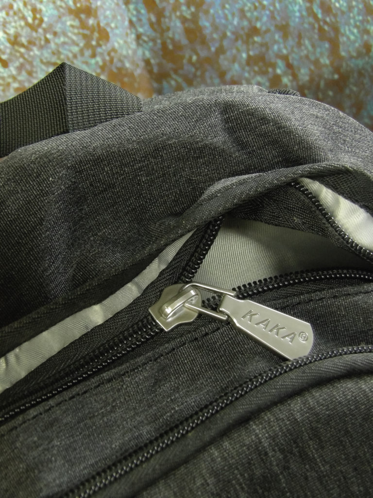 The primary zipper is discretely concealed by a fabric pleat