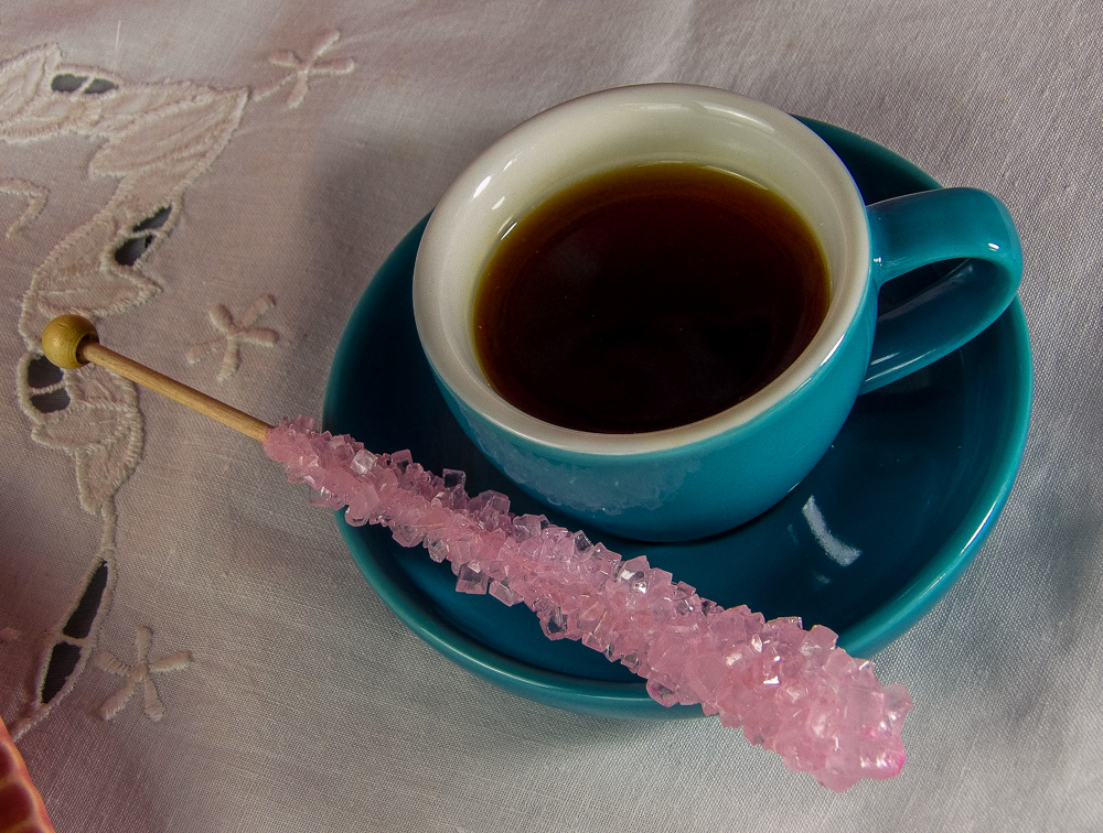 With a rock candy swizzlestick to sweeten the drink to taste.