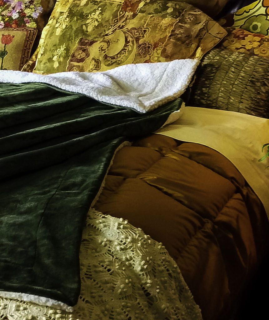 Close up of Olive Green Bedsure blanket with other bedding